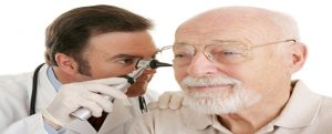 Doctor using otoscope to look in a senior man's ears.  Closeup on white.  Focus on doctor.